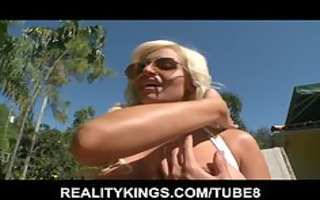 sun tanning blond shows off her large bazookas