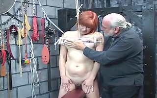 bondaged redheaded slave gets her breasts clamped