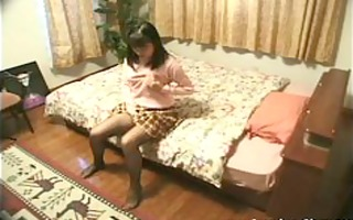 slutty oriental on the bed rubs her own tits and