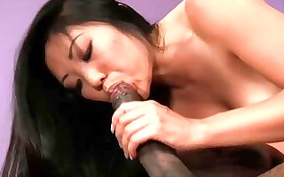 oriental hottie sits on a black rod and rides it